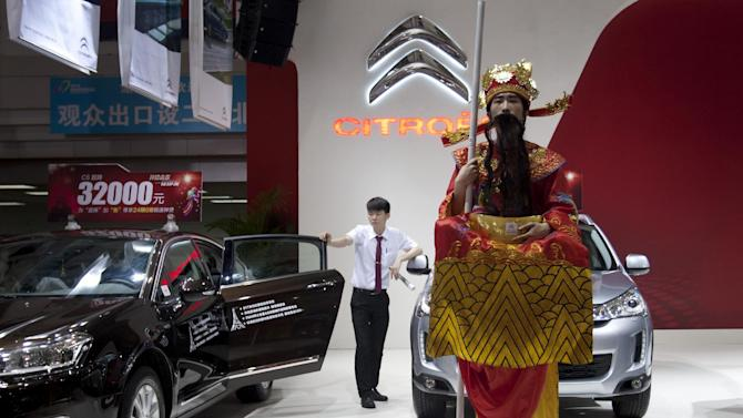 In this April 30, 2015 photo, a model dressed as the God of Fortune performs as a worker waits for customers at an auto show in Changsha, in southern China's Hunan province. June sales in the biggest car market by number of vehicles sold shrank by 3.4 percent from a year earlier as an economic slowdown deepened and smog-choked cities tried to curb growth in car ownership. Sales growth has steadily declined from 2009's explosive peak of 45 percent but the latest figures surprised analysts who were forecasting a healthy 7 to 8 percent for this year. (Chinatopix via AP) CHINA OUT