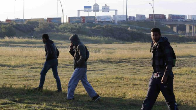 Migrants walk near the road after they left their hiding spot at the Eurotunnel site early in the morning as lorries queue to embark on shuttles at the Eurotunnel terminal in Calais