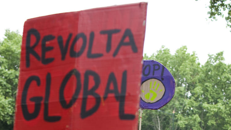 "A woman shouts slogans while another holds a sign with the words ""Global Revolt"" during an anti-austerity protest in Lisbon Saturday, May 12 2012. Hundreds took part in the demonstration organized to coincide with dozens of others being held around the globe. (AP Photo/Armando Franca)"