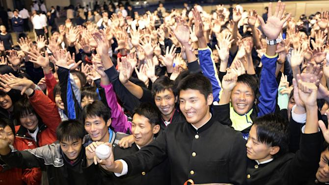 Japan's high school pitching star Tomohiro Anraku, bottom third right, smiles while posing for a photo with his classmates at Saibi High School in Matsuyama, western Japan, Thursday, Oct. 23, 2014, after he was chosen first overall in Nippon Professional Baseball's amateur draft and was headed to the former team of New York Yankees pitcher Masahiro Tanaka. The Yakult Swallows and Rakuten Eagles selected Anraku, whose fastball has been clocked as high as 97 mph (156 kph), with the first and second picks respectively, and the Eagles won a lottery for the highly touted 17-year-old right-hander. (AP Photo/Kyodo News) JAPAN OUT, CREDIT MANDATORY