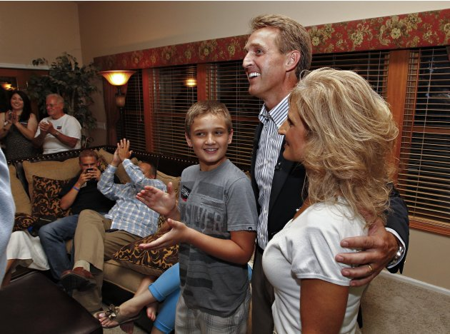 Arizona Republican Senate candidate and current U.S. Rep. Jeff Flake, R-Ariz., speaks at a primary election night party with is wife, Cheryl and son, Tanner, Tuesday, Aug. 28, 2012, at his home in Mes