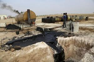 File photo of men working at a makeshift oil refinery site in Marchmarin town, southern countryside of Idlib