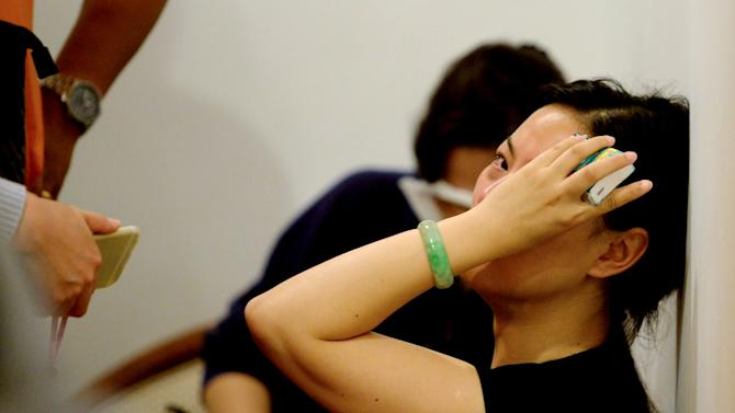 A relative of passengers on the ship which sank at the Jianli section of Yangtze River covers her face in Shanghai