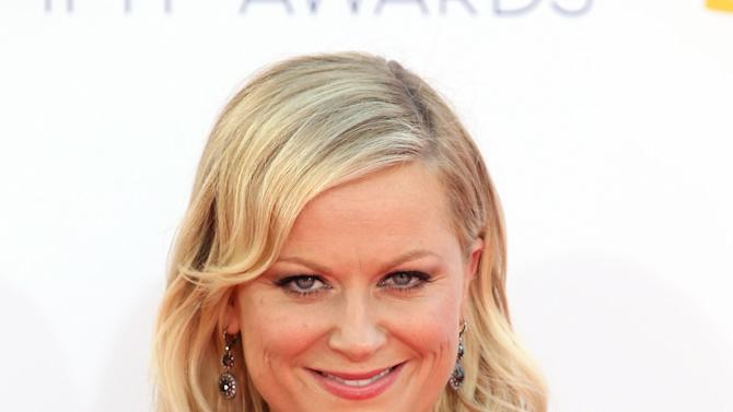 FILE - In this Sept. 23, 2012 file photo, Amy Poehler arrives at the 64th Primetime Emmy Awards at the Nokia Theatre, in Los Angeles. The Hollywood Foreign Press Association, dick clark productions and NBC announced Monday, Oct. 15, 2012, that Tina Fey and Amy Poehler, have signed on to host the 70th annual ceremony after British comedian Ricky Gervais' three-year reign as the ceremony's acerbic master of ceremonies. The Golden Globes are set to air on NBC on Jan. 13, 2013. (Photo by Matt Sayles/Invision/AP, File)