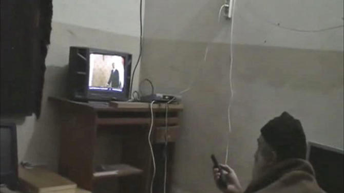 FILE - This undated image from video seized from the walled compound of al-Qaida leader Osama bin Laden in Abbottabad, Pakistan and released by the U.S. Department of Defense shows a man identified by the U.S. government as Osama Bin Laden in front of a television. Bin Laden spent his last weeks in a house divided, amid wives riven by suspicions. On the top floor, sharing his bedroom, was his youngest wife and favorite. The trouble came when his eldest wife showed up and moved into the bedroom on the floor below (AP Photo/Department of Defense, File)