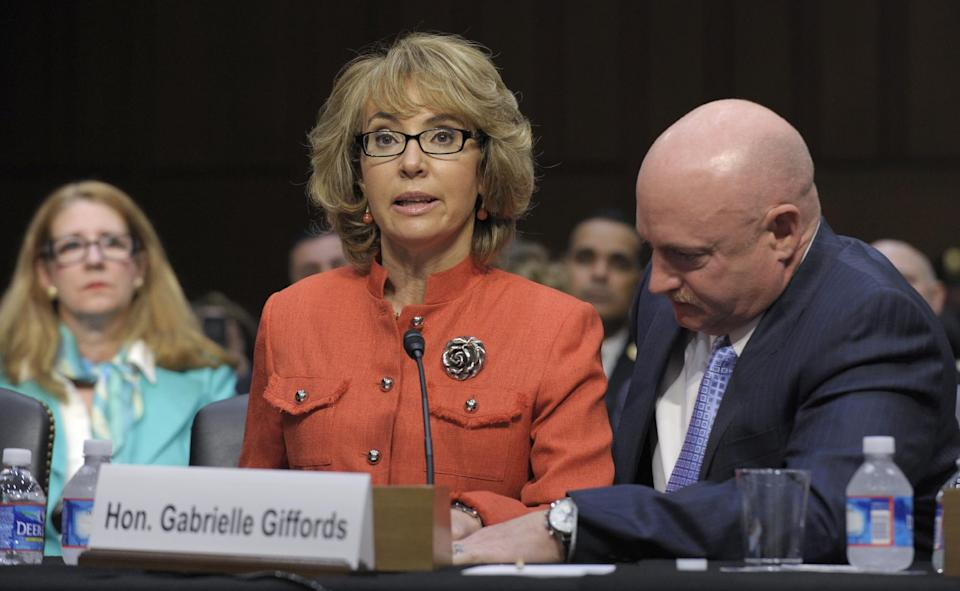 Former Arizona Rep. Gabrielle Giffords, who was seriously injured in the mass shooting that killed six people in Tucson, Ariz. two years ago, sits with her husband Mark Kelly, speaks on Capitol Hill in Washington, Wednesday, Jan. 30, 2013,  before the Senate Judiciary Committee hearing on gun violence.  (AP Photo/Susan Walsh)