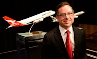 Qantas Airway CEO Alan Joyce, poses for a photo in front of a model of an Airbus A380 after the Australian flag carrier reported a doubling of first half net profit to Aus$111 million and the purchase of five new Boeing 737-800 aircraft, in Sydney, on February 21, 2013