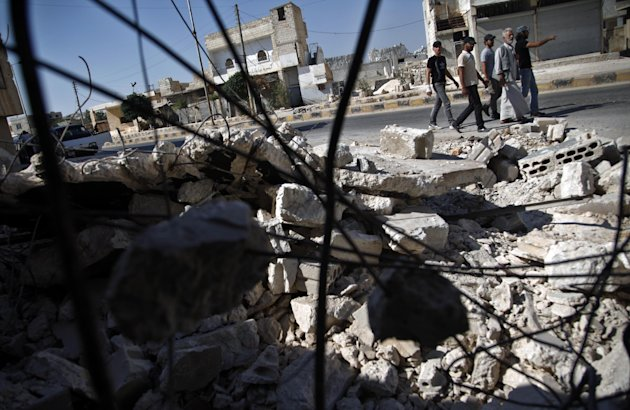 In this Sunday, Aug. 5, 2012 photograph, Syrians pass by a destroyed house in town of Atareb outskirts of Aleppo, Syria. (AP Photo)