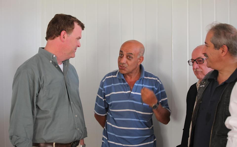 Canadian Foreign Affairs Minister John Baird, speaks to one of the Syrian refugees at Zaatari refugee camp with his  Jordanian counterpart Nasser Judeh, right,,  in Mafraq, Jordan, Saturday, Aug. 11, 2012.  (AP photo/Mohammad Hannon)