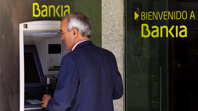 FILE - In this Friday, May 18, 2012 file photo a man uses an ATM cash point machine at a branch of the Bankia bank in Madrid. Logo says ' Welcome to Bankia'. Spain's market regulator suspended trading of shares in bailed-out Bankia on Friday May 25, 2012, ahead of a key board meeting at which the lender is expected to decide how much more rescue money it needs from the government. (AP Photo/Daniel Ochoa de Olza, file)