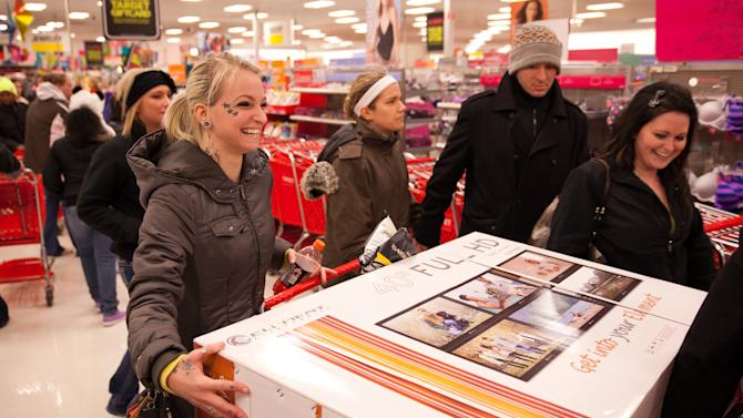 A joyful shopper laughs as she attempts to load a 40-inch TV into her cart at Target during their Black Friday sales event in Flint, Mich. on Thursday, Nov. 22, 2012. (AP Photo/Flint Journal, Griffin Moores)