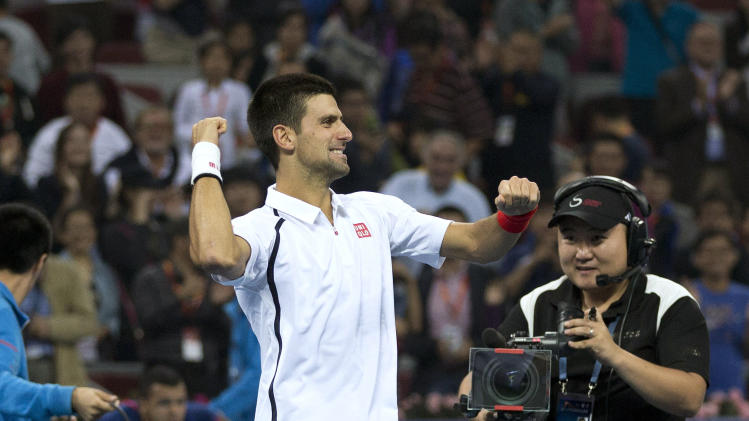 Serbia's Novak Djokovic dances on the court after defeating Jo-Wilfried Tsonga of France in the men's singles final match of the China Open tennis tournament in Beijing Sunday, Oct. 7, 2012. Djokovic defeated Tsonga 7-6, 6-2. (AP Photo/Andy Wong)