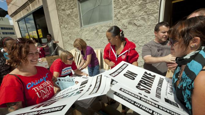 Members of the Chicago Teachers Union distribute strike signage at the Chicago Teachers Union strike headquarters on Saturday, Sept. 8, 2012 in Chicago. The union has vowed to strike on Monday, Sept. 10, 2012, should it fail to reach an agreement over teachers' contracts with Chicago Public Schools by  that date. (AP Photo/Sitthixay Ditthavong)