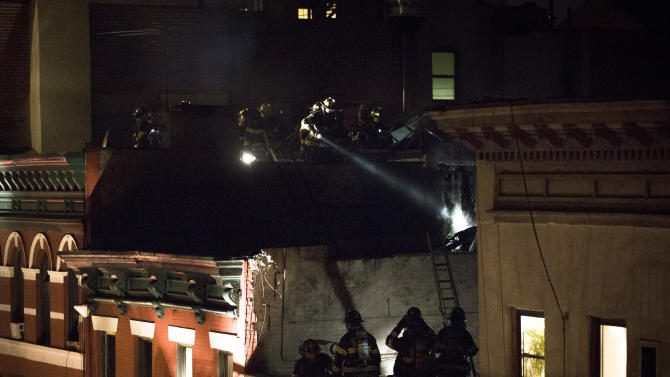 Firefighters check the rooftops above 41 Spring Street in lower Manhattan after a five-alarm fire tore through the building, Thursday, Jan. 10, 2013, in New York. One woman was killed. (AP Photo/John Minchillo)