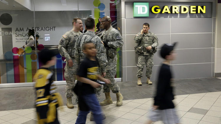 Youngs fans arrive walk past United States servicemen as they arrive to TD Garden for a Boston Bruins hockey game against the Buffalo Sabres in Boston Wednesday, April 17, 2013, in the aftermath of Monday's Boston Marathon bombings. (AP Photo/Elise Amendola)