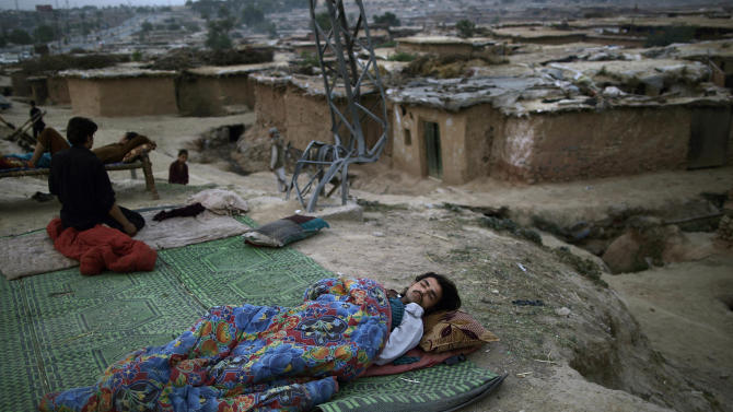 A Pakistani man, who fled his home with his family from Pakistan's tribal region of Mohmand Agency, due to fighting between the Taliban and the army, sleeps on the ground on a roadside, on the outskirts of Islamabad, Pakistan, early Monday, May 20, 2013. As the temperatures rise, many Pakistanis are sleeping outdoors to escape the heat trapped in their homes. (AP Photo/Muhammed Muheisen)