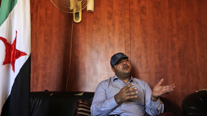 Syrian rebel commander Abu Ibrahim, whose real name is Ammar al-Dadikhli, gestures during an interview with The Associated Press at Bab Al-Salameh border crossing, near the Syrian town of Azaz, Thursday, Sept. 13, 2012. Ibrahim, who is holding 10 Lebanese Shiites hostage, said Thursday he is willing to release the men but fears it could provoke attacks by Sunni extremists who would disagree with his decision. (AP Photo/Muhammed Muheisen)