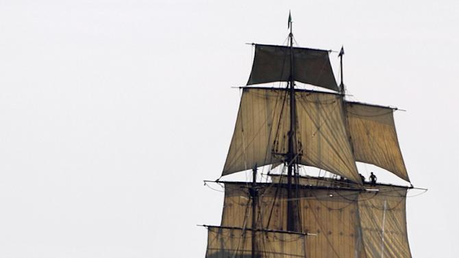 FILE - In this July 9, 2012, file photo, a replica of the historic ship HMS Bounty, right, sails past a lighthouse, center, as it departs Narragansett Bay and heads out to sea off the coast of Newport, R.I. The Coast Guard aid Monday, Oct. 29, 2012, that the 17 people aboard the HMS Bounty have gotten into two lifeboats, wearing survival suits and life jackets. The HMS Bounty, a tall ship, was in distress off North Carolina's Outer Banks as Hurricane Sandy swirls toward the East Coast. (AP Photo/Steven Senne, File)