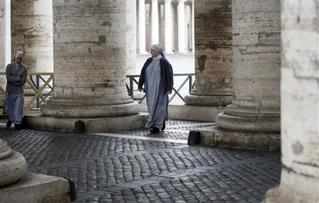 Nuns walk through the colonnade at Saint Peter's square at the Vatican