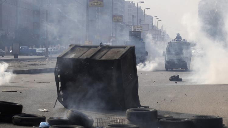 Protesters block a road during clashes with riot police in Cairo