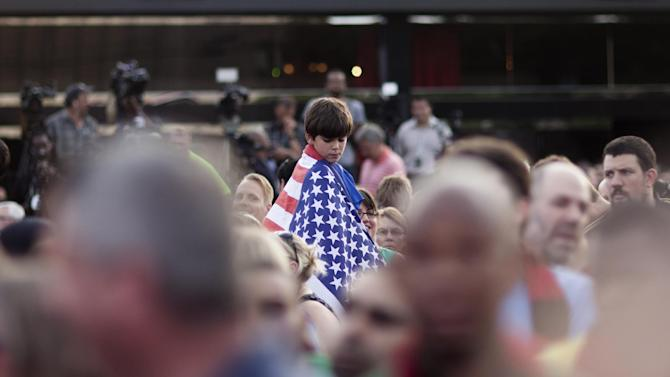 A boy wears a flag during a party at which an MLS expansion team's name, Atlanta United FC, was announced, Tuesday, July 7, 2015, in Atlanta. The team will begin to play in 2017 at the city's new retractable roof stadium. (AP Photo/Branden Camp)