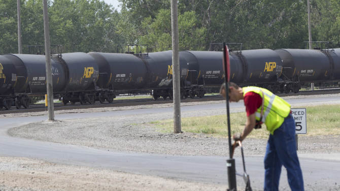 In this Aug. 8, 2012 photo, a worker is seen as DOT-111 and AAR-211 class rail tankers pass by at the Union Pacific rail yard in Council Bluffs, Iowa. For two decades, DOT-111 rail tankers have been allowed to haul hazardous liquids from coast to coast even though transportation officials were aware of a dangerous design flaw that almost guarantees the car will tear open in an accident. The rail and chemical industries have committed to a safer design for new tankers, but they do not want to modify tens of thousands of existing cars. That's despite a spike in the number of accidents. (AP Photo/Nati Harnik)