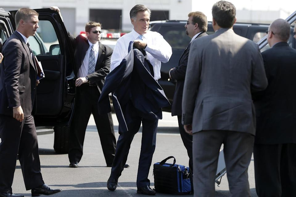Republican presidential candidate, former Massachusetts Gov. Mitt Romney puts on his jacket before boarding his campaign charter plane in Newark, N.J., Friday, Sept. 14, 2012. (AP Photo/Charles Dharapak)