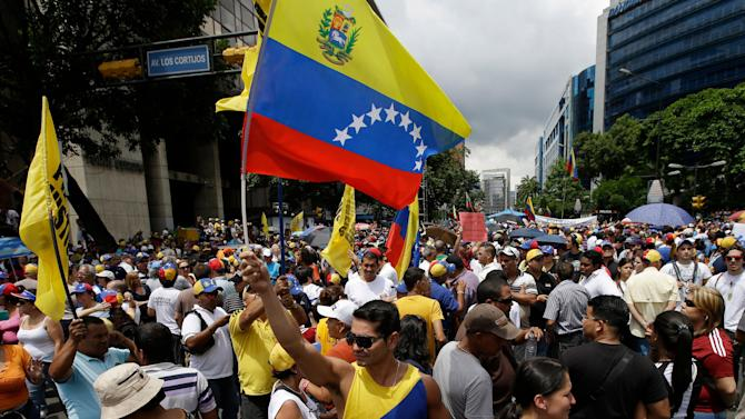 In this May 1, 2013 photo, members of the opposition hold Venezuelan flags during a May Day march in Caracas, Venezuela. Venezuelans have long been obsessed by politics, especially during the Chavez years, as the populist leader denounced his opponents as ìthe squalid onesî and the opposition tried vainly to oust him through a coup and a referendum. Many, however, say the tensions have reached a pitch not seen here since that 2002 coup, which briefly pushed Chavez from office. (AP Photo/Fernando Llano)