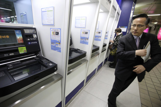 A depositor leaves after checking his account through an automated teller machine at a subway station as the bank's computer networks was paralyzed in Seoul, South Korea, Wednesday, March 20, 2013. Po
