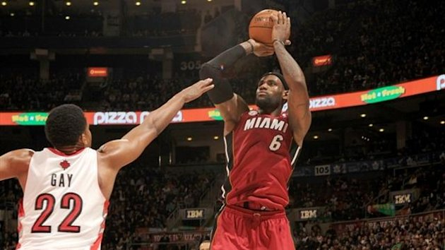LeBron James #6 of the Miami Heat goes for a jump shot against Rudy Gay #22 of the Toronto Raptors