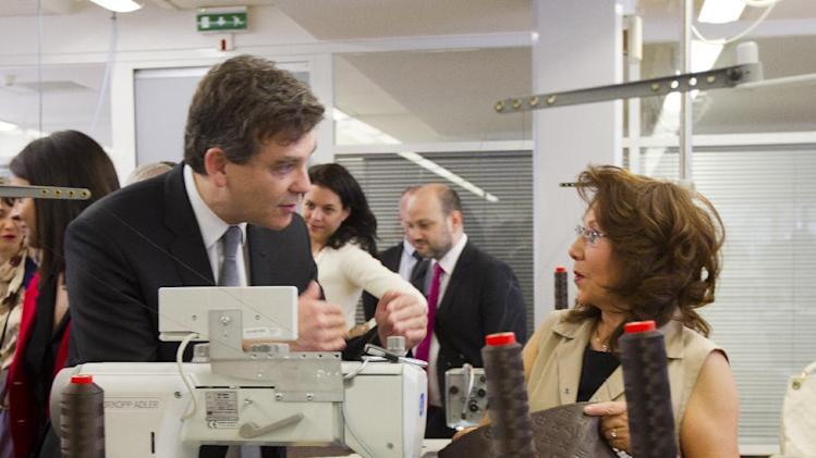 "French Minister for Industrial Recovery Arnaud Montebourg talks to workers during a visit of ""Particular operation days"" in LVMH, the world's largest luxury company at the factory of Vuitton, in Asnieres, France, north of Paris Saturday June 15, 2013.(AP Photo/Jacques Brinon)"