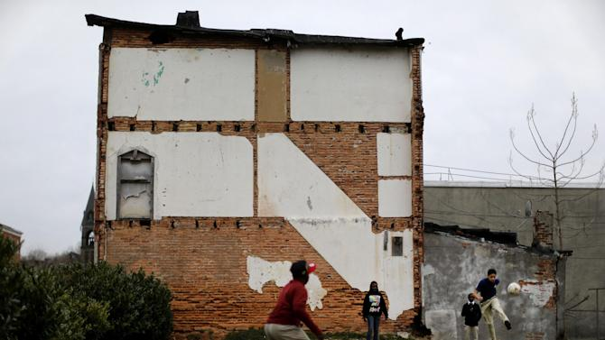 In this April 4, 2013 picture, children play kickball on a vacant lot alongside a blighted row house in Baltimore. The U.S. Census Bureau estimates that 20 percent of American children are impoverished. (AP Photo/Patrick Semansky)