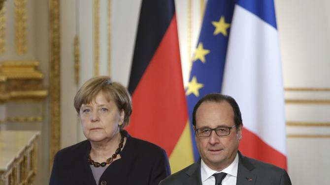 French President Hollande arrives with German Chancellor Merkel to attend a press conference at the Elysee Palace in Paris