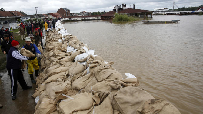People build a dam made up of sandbags by the bank of the Sava river in Sremska Mitrovica, 90 kilometers west of Belgrade, Serbia, Saturday, May 17, 2014. Record flooding in the Balkans leaves at least 20 people dead in Serbia and Bosnia and is forcing tens of thousands to flee their homes. Meteorologists say the flooding is the worst since records began 120 years ago. (AP Photo/Darko Vojinovic)