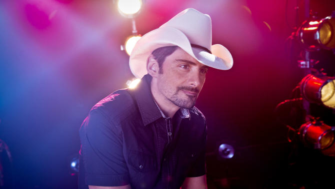 """American country singer-songwriter and musician Brad Paisley poses for a portrait, Thursday, Aug. 28, 2014, in New York. Paisley cranks up the fun and avoids controversy on his new album """"Moonshine in the Trunk."""" (Photo by Amy Sussman/Invision/AP)"""