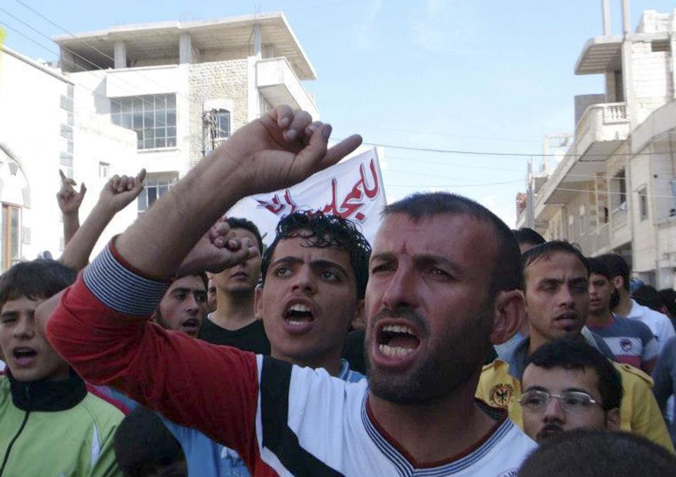 In this citizen journalism image provided by Edlib News Network, ENN, which has been authenticated based on its contents and other AP reporting, anti-Syrian regime protesters shout slogans during a demonstration at Binnish village, in Idlib province, northern Syria, on Friday Oct. 12, 2012. (AP Photo/Edlib News Network ENN)