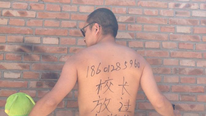 """In this photo taken Wednesday May 29, 2013 and released by Beijing-based poet Wang Zang Monday, June 3, 2013, Wang poses at his work place in Beijing with the Chinese characters """"Principal, get a room (with me). Leave the young students alone,"""" scribbled on his back while holding a toy and a liquor bottle. The unusual outpouring is in response to a recent spate of sex abuse cases, including that of a school principal who spent the night in a hotel room with four underage girls. Artists, activists, university students and police officers are photographing themselves - some nude and provocatively posed, some angry and menacing - with the message. (AP Photo/Courtesy of Wang Zang)"""
