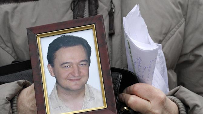 FILE - In this Nov. 30, 2009 file photo, Nataliya Magnitskaya holds a portrait of her son, Russian lawyer Sergei Magnitsky, a lawyer who died in jail, as she speaks  with The Associated Press in Moscow, Russia. The Treasury Department on Friday announced the names of 18 Russians subject to financial sanctions and visa bans because of their alleged violations of human rights. The list, an outgrowth of a law enacted last December to hold Russian officials accountable for human rights abuses, is certain to further strain relations with the Moscow government. Russia has strongly objected to the act and threatened to retaliate with its own sanctions. The act is named for  Magnitsky, who was arrested in 2008 for tax evasion after accusing Russian police officials of stealing $230 million in tax rebates. He died in prison the next year, allegedly after being beaten and denied medical treatment.  (AP Photo/Alexander Zemlianichenko, File)