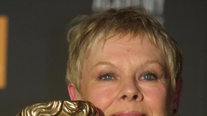 "FILE - In this Feb. 24, 2002 file photo, British actress Dame Judi Dench poses with her 2002 British Academy of Film and Television Arts (BAFTA) award for best actress in a leading role for her portrayal of novelist Iris Murdoch in the film ""Iris,""  at the award ceremony in London.  (AP Photo/Alastair Grant, File)"