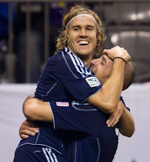 Sporting Kansas City's Chance Myers, left, and Aurelien Collin, of France, celebrate Kei Kamara's goal against the Vancouver Whitecaps during the second half of an MLS soccer game in Vancouver, British Columbia, on Wednesday, April 18, 2012. (AP Photo/The Canadian Press, Darryl Dyck)