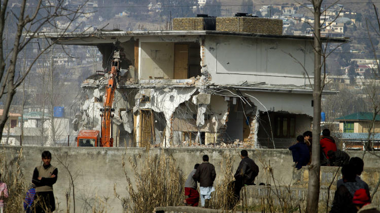 Local residents watch as authorities use heavy machinery to demolish the compound of Osama bin Laden in Abbottabad, Pakistan on Sunday, Feb. 26, 2012. Pakistan was more than halfway done Sunday demolishing the three-story compound where bin Laden was killed by U.S. commandos last May, erasing a concrete reminder of a painful and embarrassing chapter in the country's history.   (AP Photo/Anjum Naveed)
