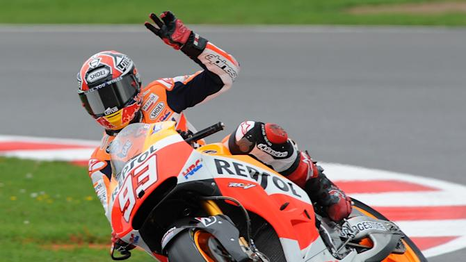 Spain's Marc Marquez of Repsol Honda waves to fans after qualifying in pole position during Moto GP qualifying session for the British Grand Prix at Silverstone, England, Saturday, Aug. 30, 2014. (AP Photo/Rui Vieira)