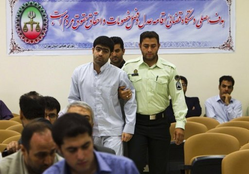 <p>An Iranian policeman leads Majid Jamali Fashi, the man convicted of the assassination of the nuclear scientist Masoud Ali Mohammadi, to his trial at Tehran's Revolutionary Court on August 23, 2011. Iran executed Jamali Fashi on Tuesday</p>