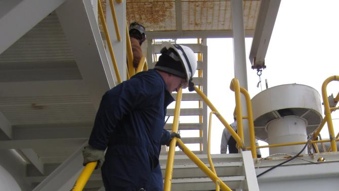This Jan. 10, 2013, photo provided by the U.S. Coast Guard shows an inspector climbing damaged stairs during an inspection aboard the Shell Arctic drilling rig Kulluk in Kiluida Bay, near Kodiak, Alaska. The rig grounded on Sitkalidak Island on Dec. 31, 2012, and was towed to Kiliuda Bay Jan. 7, 2013. The unified command overseeing salvage of the rig says it will release minimal information on the vessel until an assessment is complete. (AP Photo/U.S. Fish and Wildlife Service)