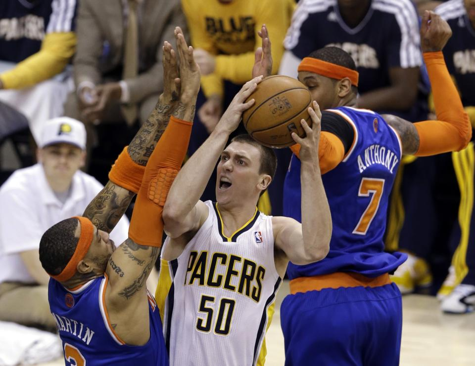 Indiana Pacers forward Tyler Hansbrough (50) shoots between New York Knicks forwards Kenyon Martin, left, and Carmelo Anthony during the first half of Game 3 of the Eastern Conference semifinal NBA basketball playoff series in Indianapolis, Saturday, May 11, 2013.  (AP Photo/Michael Conroy)