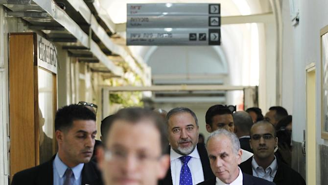 Former Israeli Foreign Minister Avigdor Lieberman, center, walks towards a courtroom at the Magistrate Court in Jerusalem, Wednesday, Nov. 6, 2013. An Israeli court has found former Foreign Minister Avigdor Lieberman not guilty of all charges in a graft trial. (AP Photo/Ronen Zvulun, Pool)