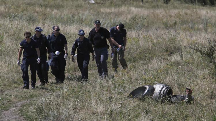 Members of a group of international experts walk past wreckage at the site where the downed Malaysia airlines flight MH17 crashed in Donetsk region