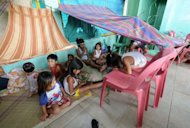 Children play inside an evacuation centre in Navotas City, suburban Manila on August 2, 2012, after heavy rains and strong winds were brought about by Typhoon Saola
