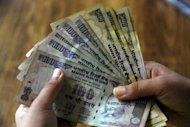 An Indian banker counts out 100 and 500 rupee banknotes in Kolkata. The Indian rupee has fallen to a new record low against the dollar, breaching the 57 rupee mark for the first time, as global uncertainty pushed investors to the safe-haven US currency