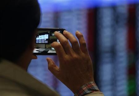 A visitor takes pictures in front of an electronic board showing stock prices at Tokyo Stock Exchange (TSE) in Tokyo April 24, 2013. REUTERS/Yuya Shino
